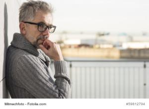 Grauhaariger Mann mit schwarzer Brille