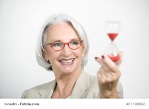Weißhaarige Dame mit roter Brille